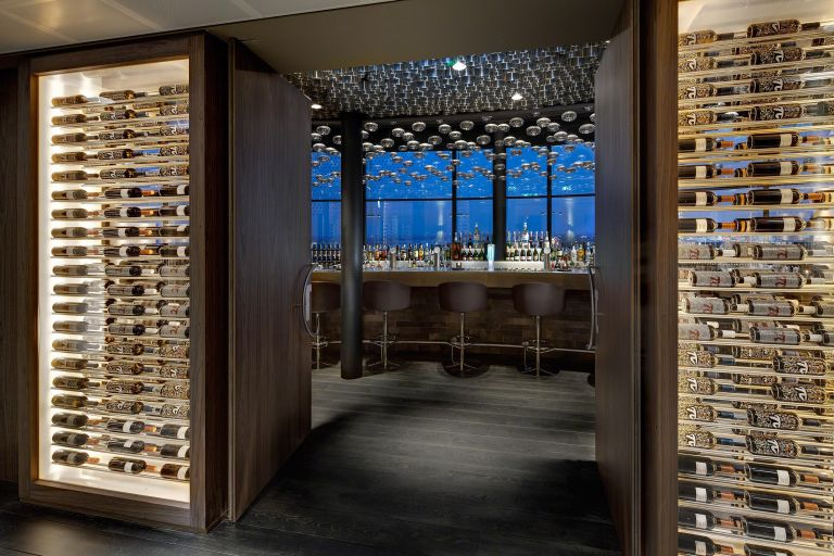 Wine climate cabinets and luxury walnut folding doors offer a view through into the sky bar of Amsterdam's Fletcher design hotel.