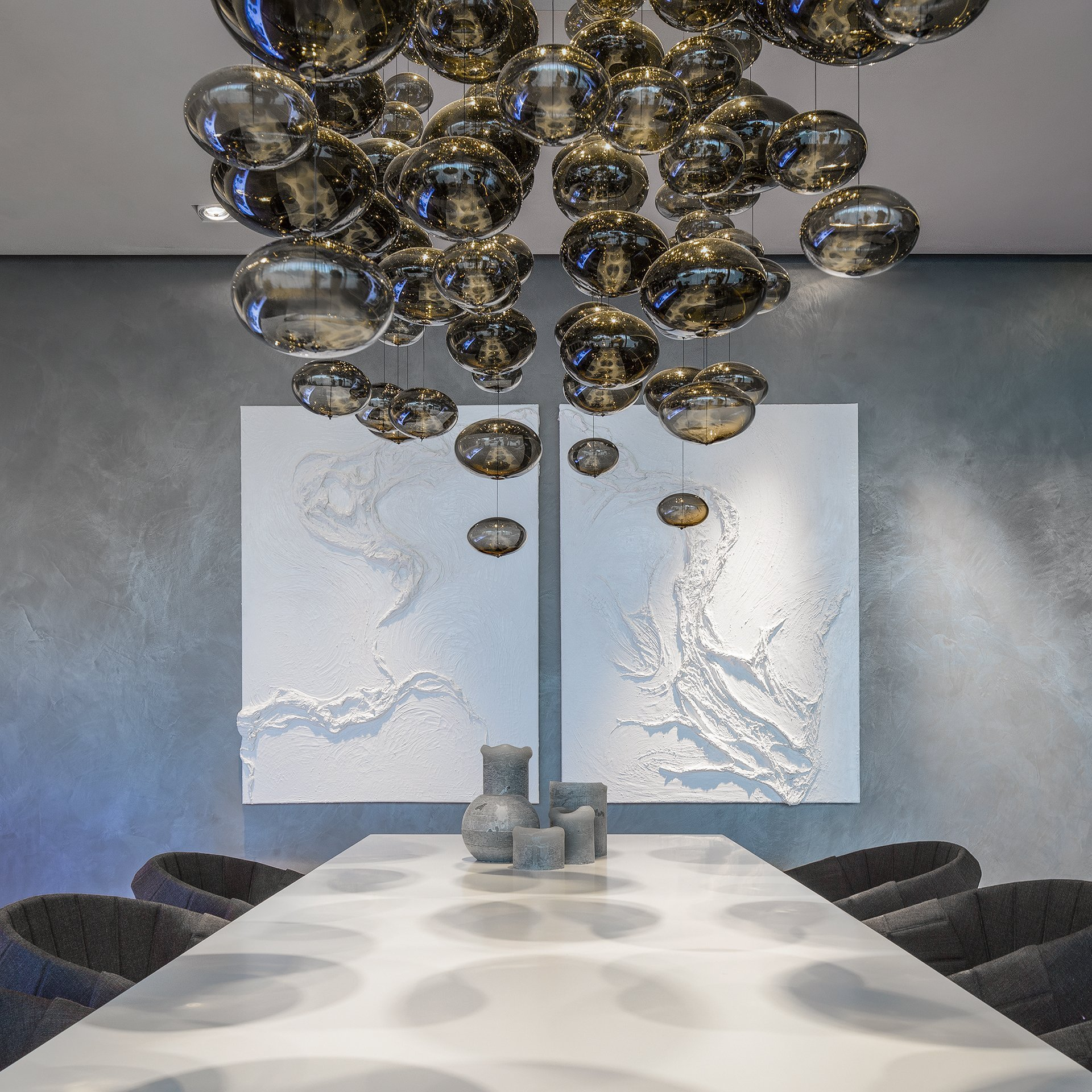 'Dream' chandelier hangs above 'b'oom' design table, with a diptych artwork on the wall featuring unusual stucco work.