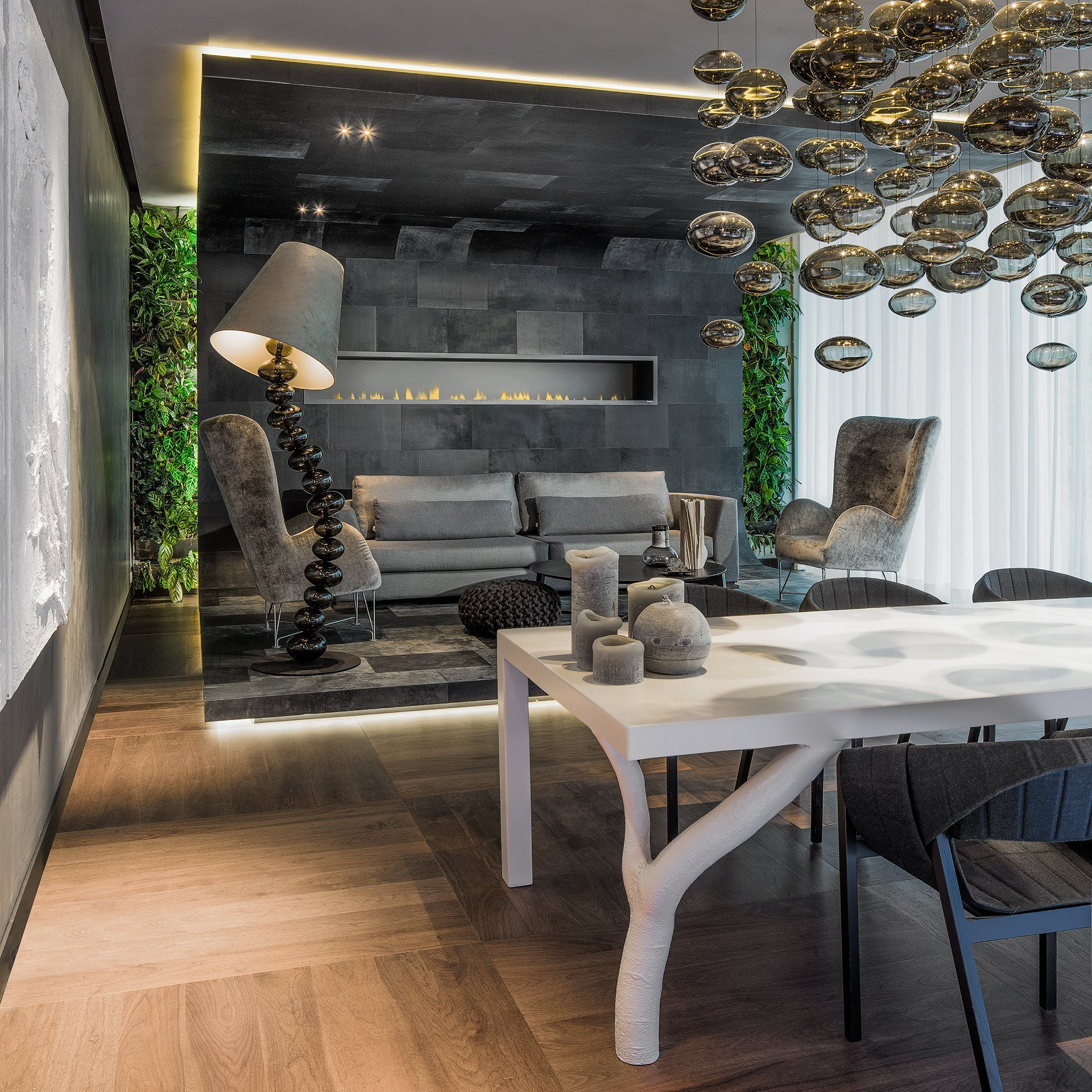 Seating area with Alphenberg leather upholstery set in front of a living wall, with a white design conference table in the foreground.