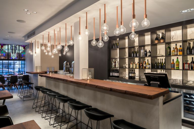 Bar design with indirectly-lit alabaster rear bar wall. Fashioned from a tree trunk, the bar is set on a concrete base.