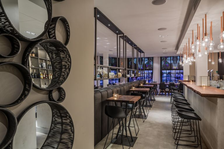 Round mirror offers a view through to the bar, where the copper hanging lamps create an intimate mood.